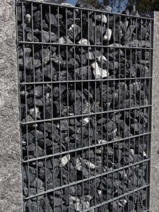 Gabionenzaun mit dunklen Steinen